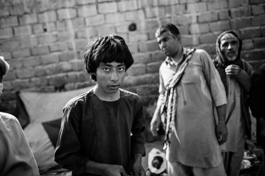 A youngster, addicted to heroin, stands with fellow addicts near the cemetery in Zaranj, Nimroz.